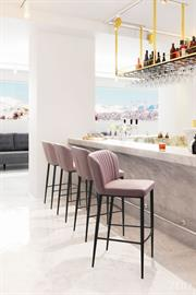 A flared back and channeled tufting gives this bar chair an art deco vibe. Pull it up to your bar height table or kitchen island to create a swanky setting. Slim steel legs give it simple style and stability. Support slats provide a comfortable footrest while seated.