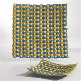 Seemingly simple, this Basket Weave Charger is a work of complex art. The multi-layer process involves weaving strips of fused glass together, then baking them. The final product is a coupe shaped charger in blue and yellow with beautiful texture.