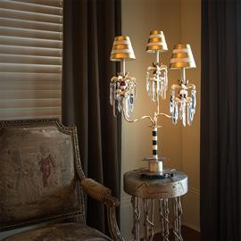 Three-tier candelabra with black, cream and gold stripes and cream and gold striped parchment shades.