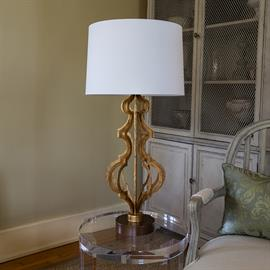 The gold metal frame of the Octavia table lamp creates a striking silhouette. It is finished with a bronze resin base and white cotton cylinder shade.