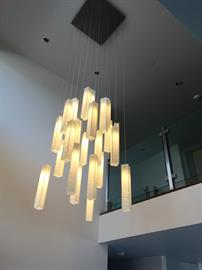 "WHITE CANDLES CHANDELIER. A unique beautiful Custom long pendants chandelier by Galilee lighting. This beautiful chandelier is designed with our ""White candles"" pendants in a two levels story space, and definitely make a statement in the entrance. The chandelier can be designed in any size, color, and number of pendants, for any space, commercial or residential. To receive our catalog by email, contact Sales@GalileeLighting.com We deliver worldwide. We invite you to visit our custom unique modern lighting"