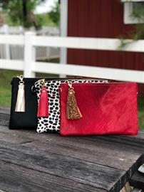 Our Brazillian cowhide clutches are stunning and there are no two alike.  The clutches are hand crafted here in Texas and measure approximately 13x9.  They have gold tabs on each side for maximum versitity and the ability to carry it 3 ways!  You can carry it as a clutch, or add your favorite wristlet or cross body strap.