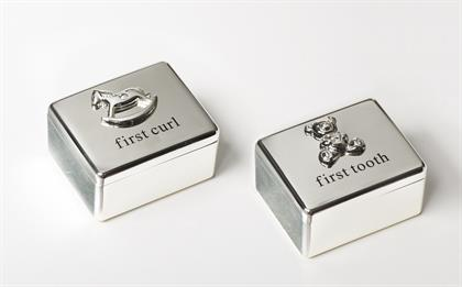 "Stash away the treasured baby's first curl and tooth in Roman's new, sleek keepsake boxes. Each box features an iconic metal relief with crystal. Perfect baby shower gifts that will quickly become heirlooms! Measures: 2"" W."