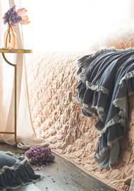 Loulah Large Throw Blanket in Powder, draped over Luna Coverlet in Rosegold.