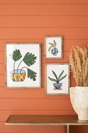 Set of three colorful plant prints under glass