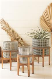 Set of three woven metal planters with wood stands