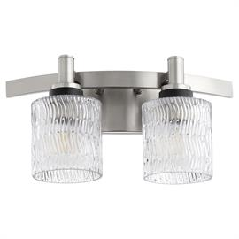 The Stadium vanity light combines classic styling with modern accents for a fashion-forward look. This fixture boasts a Satin Nickel finish, as well as clear chiseled cylinder glass shades that will provide your washroom with a sleek and sophisticated look. This luminary can fit any decor style, given that it offers transitional appeal in its sophisticated composition. This fixture comes equipped with three different socket accessory finish options: Aged Brass, Noir, and Satin Nickel, so you can customize