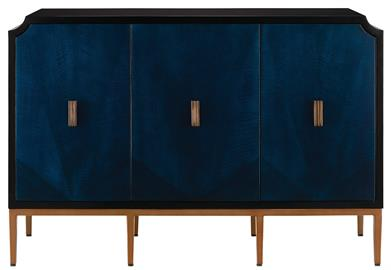 The Kallista Cabinet has a dark sapphire blue finish that enlivens the sycamore veneers on its door fronts. The wood grains bring the cabinet a hint of distressing that contrasts the sleek lines of the base and door pulls in an antique brass finish. The exterior is finished in a glossy caviar black. Design details on this navy blue cabinet include soft-close door hinges, and adjustable shelves and glides. The Kallista family of products includes a number of pieces.