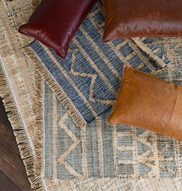 Geometric patterns accent the distressed color palettes of this handwoven jute rug. Fringe details add to its casual charm.